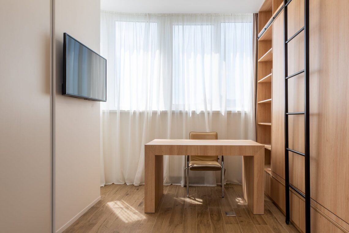 wooden table with chair near cupboard in study room